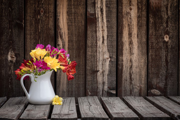 A bunch of colorful freesia flowers in a white ceramic pitcher on a rustic wooden plank table.