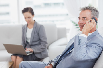 Businessman on the phone while his colleague working on her laptop