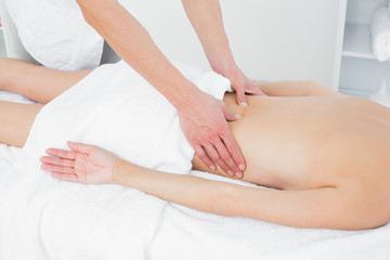 Mid section of a physiotherapist massaging womans back