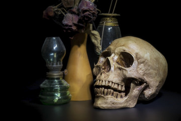 Still life photography with human skull on dark background