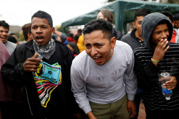 Members of a caravan of migrants from Central America react near the San Ysidro checkpoint as the first fellow migrants entered U.S. territory to seek asylum on Monday, in Tijuana,