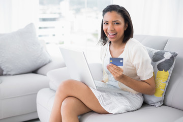 Laughing young dark haired woman in white clothes shopping online with a laptop