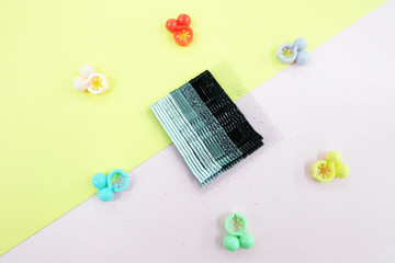 Hair Accessories Gradient Black Hairpin Set. Fashion Black Hair Clips Isolated on Pink and Yellow Background