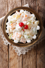 fruit salad Ambrosia from pineapple, tangerine, grapes and marshmelow close-up. Vertical top view