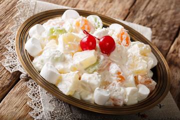 Organic healthy fruit salad Ambrosia with marshmallow and vanilla yogurt close-up. horizontal