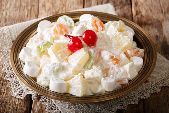 fruit salad from pineapple, oranges, grapes and coconut with marshmallow and vanilla yogurt close-up. horizontal