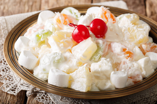Summer Ambrosia delicious salad of fruits and marshmelow with vanilla yogurt close-up on a plate. horizontal