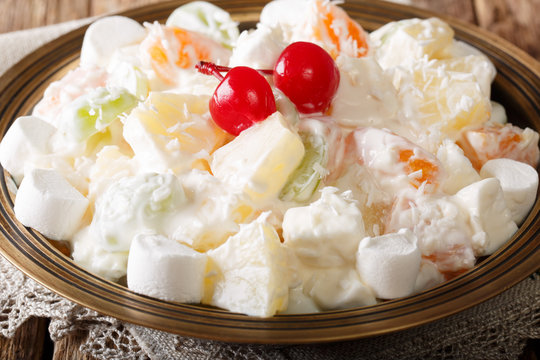 Dessert fruit salad Ambrosia from pineapple, tangerine, grapes and marshmelou with vanilla yogurt close-up. horizontal