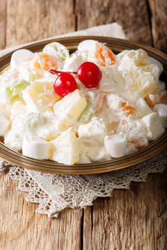 Delicious salad Ambrosia made from pineapple, tangerine, grapes and marshmelou with vanilla yogurt close-up on a plate. vertical