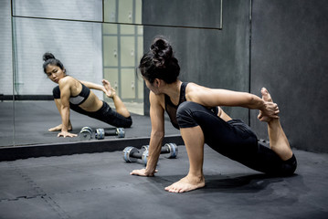 Young Asian woman doing exercise in fitness gym after weight lifting with dumbbell. Healthy lifestyle concept