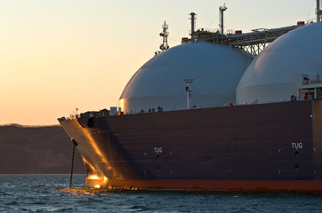 The bow of a huge LNG carrier at anchored in the roads.