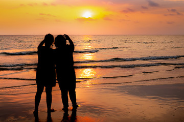 Silhouette couple on the beach sunset background