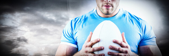 Rugby player looking at camera with ball against spotlight in sky
