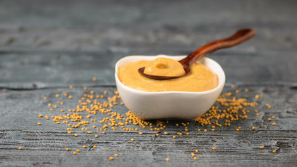 Scattered mustard seeds and a bowl of sauce on a dark rustic table.