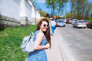 young pretty woman in blue dress and sunglasses walking in sunny day