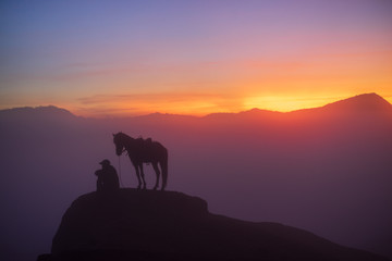 Silhouette of unidentified local people or Bromo Horseman at the mountainside of Mount Bromo, Semeru, Tengger National Park, Indonesia.
