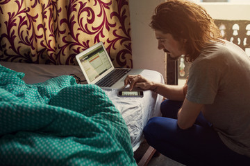 Young traveller man sitting near bed with laptop in hotel room