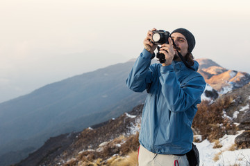 Hiker staying on snow mountain top above clouds and valley, doing pictures on small photo camera