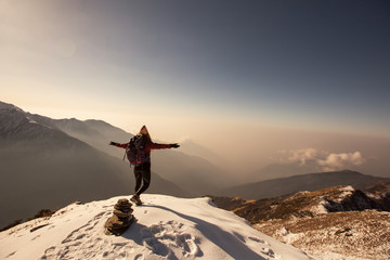 Female Traveller relaxing above clouds on top of snow high mountain and enjoying view of valley, freedom travel concept, nepali style hat, sunrise