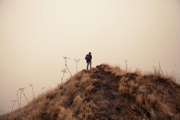 Hiker man walking in mist fog mountain top