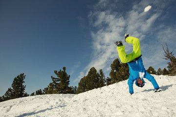 Guy have fun and stand on his hands on snow mountain top. Snowboard, freeride and winter holiday