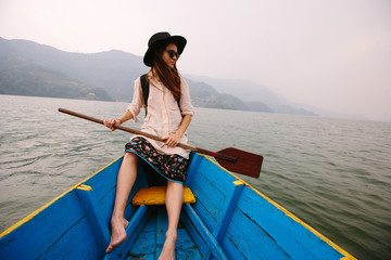 Woman in black hat sitting on boat with paddle, nice mountain lake Fewa on background