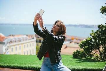Woman doing selfie using smart phone traveling and walking outdoor in sunny day, European city