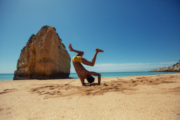 silhouette of young happy man on ocean shore doing capoeira and enjoying summer holiday. Dark skin, mixed race, black African hairstyle