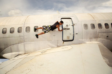 Young man holding airplane door from outside and hangs in the air. Aircraft crash, extreme flight