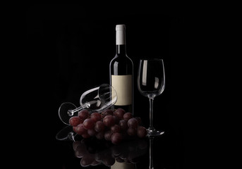 Red wine bottle, two empty wine glasses and grape on black background