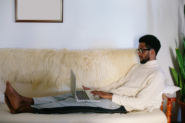 Portrait of young freelancer black man wearing glasses seating on sofa using laptop at home
