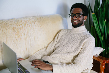 Portrait of young smiling black man wearing glasses seating on sofa using laptop at home