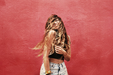 Fun and colorful. Young pretty happy woman with long wavy hair on her face posing and smiling against pink wall