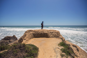 Portrait of African man standing on beautiful cliff, looking to ocean, enjoy motor travel holiday. Algarve, Portugal