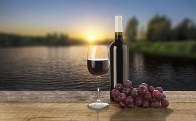 Red wine bottle,  wine glass and grape on sunset background