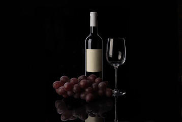 Red wine bottle, empty wine glass, corkscrew and grape on sunset background
