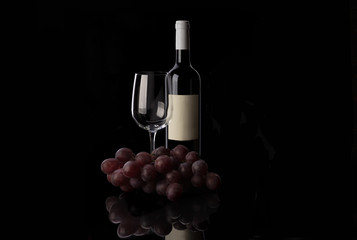 Red wine bottle, empty wine glass and grape on black background