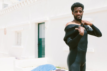 Mixed race surfer man taking off wetsuit after surfing lessons