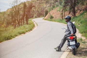 Mixed race with dark skin biker wearing helmet sitting on motorcycle on mountain road, enjoy and relaxing in his motor travel