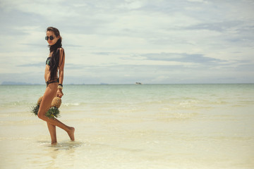 Beautiful happy female with very long hair holding pineapples on sea shore, enjoy summer and water