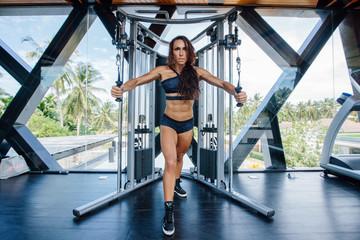 Beautiful Athlete female doing exercises in gym