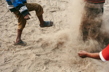 Children have fun on river beach, fight by sand, playing, throwing. Dark skin, happy childhood