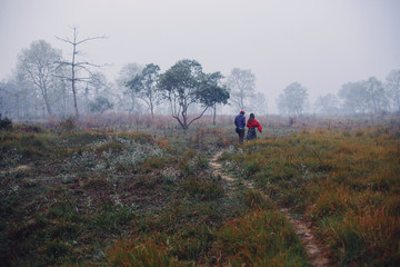 Travel couple walking in fog field, jungle forest, fresh morning time. Chitwan national park, Nepal