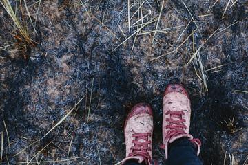 female legs wearing pink sneakers standing on black burned grass outdoor