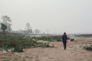 Traveller man walking outdoor with dogs. Morning Fog landscape, river shore