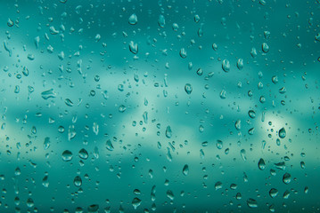 Blue water drops on window glass after rain. Cloud Background