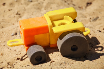 A toy plastic tractor on the sand of a playground. Vehicle close-up.