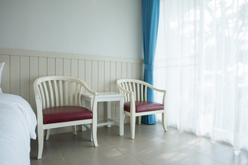 Set of chairs in the hotel is by the window with white curtain and sunshine