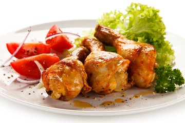 Grilled chicken drumsticks on white background