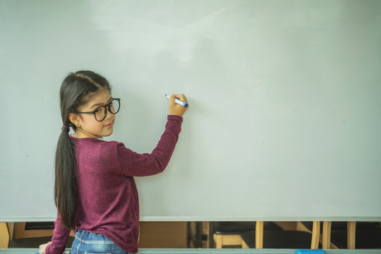 Asian girl writing on empty white board in class room at school